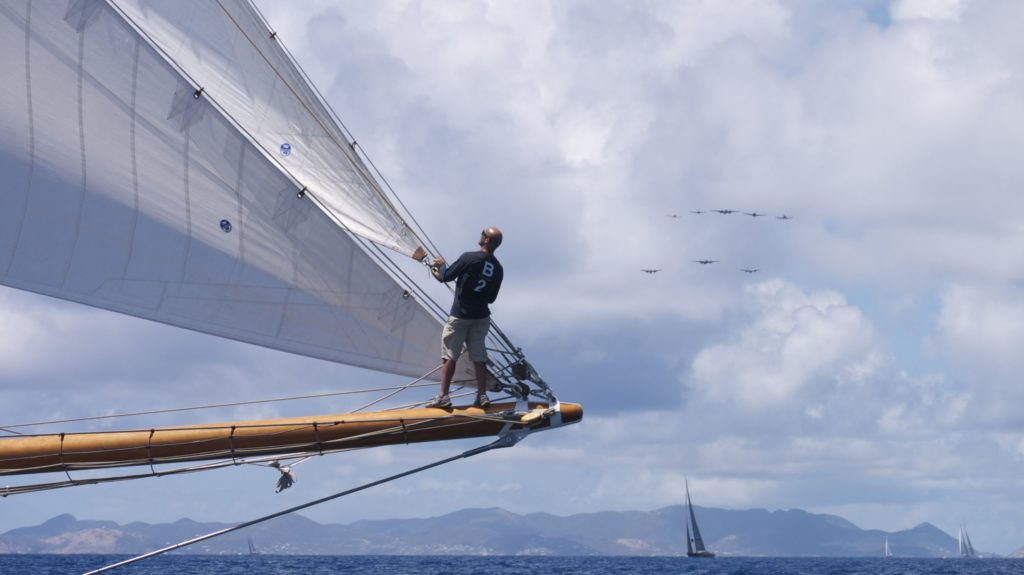Crew on bowsprit of superyacht off St Barths, ready for the race